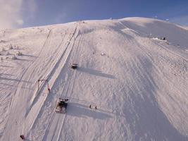 Snowcat yoke ski lift overhead top view of snowed slope photo