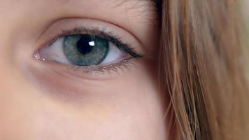 Girl's eye close up of blue color looking at the camera. Concept of childhood, youth, kids protection, memories video