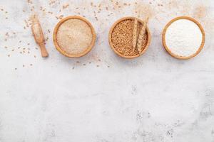 Wheat grains , brown wheat flour and white wheat flour in wooden bowl set up on white concrete background. photo