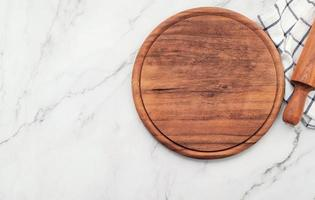 Empty wooden pizza platter with napkin and rolling pin set up on marble stone kitchen table. Pizza board and tablecloth on white marble background. photo