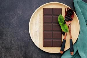 Food conceptual image with dark chocolate and fork on dark concrete background. photo