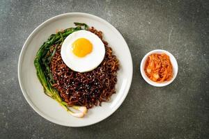 dried Korean spicy black sauce instant noodles with fried egg and kimchi photo