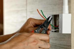 Electrician is stripping electrical wires in a plastic box on a wooden wall to install the electrical outlet. photo
