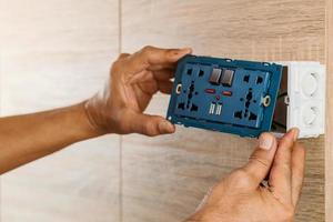 Hand of an electrician are installing the universal wall outlet AC power plug with USB port and on-off in a plastic box on a wooden wall. photo