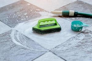 Close up the green plastic brush for scrubbing and cleaning the floor is placed on the wet tile floor and foamed with detergent. photo