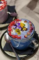Cups of blue matcha decorated with edible flowers, rose petals and glitter photo
