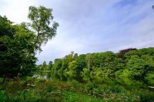 Hermoso paisaje de follaje de árboles y el estanque de peces en el área de Harewood House Trust en West Yorkshire en el Reino Unido foto