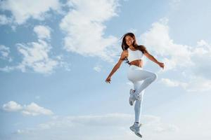 Against blue sky. Posing for the camera. Young fitness woman with slim body type is outdoors photo