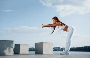 Shot of sportive woman doing fitness exercises near the lake at daytime photo