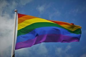 International pride festival flag on blue sky background photo
