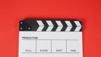 claqueta o pizarra de película. Se utiliza en producción de video, cine, industria cinematográfica sobre fondo rojo. foto