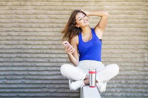 Girl drinking from a metal water bottle wearing casual clothes photo