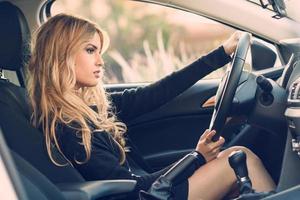 Blondie joven conduciendo un coche deportivo foto