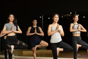 Yoga class of young people interested in yoga activities With a yoga teacher photo