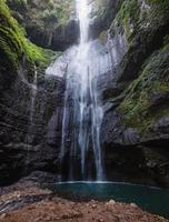 Majestic waterfall flowing on rock cliff in rainforest photo