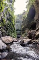 Majestic waterfall flowing on rocky cliff in tropical rainforest photo