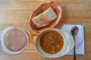 Traditional Icelandic and Scandinavian lamb meat soup with white bread in wooden plate and glass of beer, Iceland, closeup, details. photo