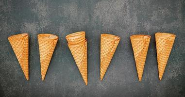 Flat lay ice cream cones collection on dark stone background . Blank crispy ice cream cone with copy space for sweets menu design. photo