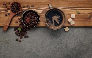 Roasted coffee beans with coffee cup setup on dark stone background. photo