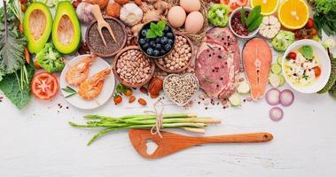 concepto de dieta cetogénica baja en carbohidratos. ingredientes para la selección de alimentos saludables sobre fondo blanco de madera. foto