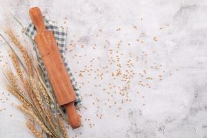 Wheat ears and wheat grains setup with rolling pin on white concrete background. photo