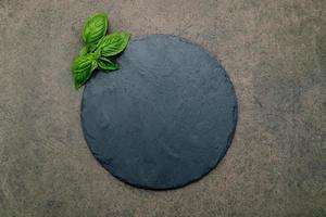 bandeja de pizza vacía para hornear casera sobre hormigón oscuro. concepto de receta de comida en textura de fondo de piedra oscura con espacio de copia. foto