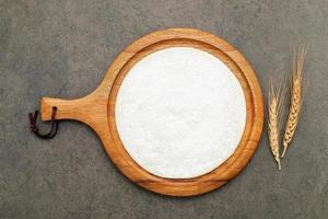 Thin homemade pizza dough with wheat ears  set up on dark concrete background. photo
