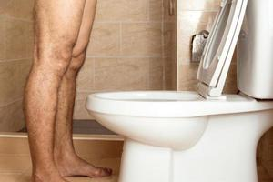 A man standing urinating in the toilet. photo