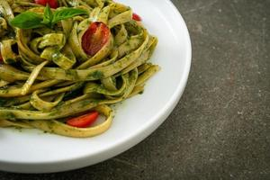 fettuccine spaghetti pasta with pesto sauce and tomatoes photo