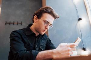 Primer plano del hombre recibió buenas noticias en el teléfono inteligente, el hombre descansando en la cafetería y enviando mensajes de texto nuevos mensajes de correo, fondo borroso, someras DOF foto
