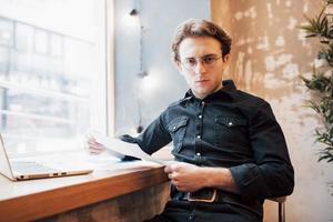 Relajado joven profesional navegando por internet en su portátil en un café foto