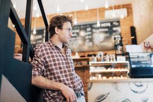 joven pensativo está sentado en la tienda de confitería. ella está tomando café mientras espera a alguien foto