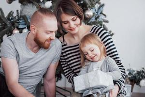Happy family at christmas in morning opening gifts together near the fir tree. The concept of family happiness and well-being photo