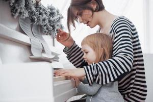 madre e hija tocando el piano blanco, vista de cerca foto
