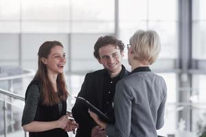 concepto de negocio, tecnología y oficina - sonriente jefa hablando con el equipo de negocios foto