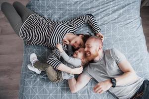 Vista superior de la hermosa joven madre, padre e hija mirando a la cámara y sonriendo mientras está acostado en la cama cabeza a cabeza foto