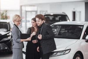 Ready to ride. Gorgeous loving couple posing together near their new car at the car dealership showroom salon smiling happily showing their car keys transport vehicle rental buying wellbeing lifestyle photo