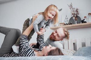 feliz madre de familia, padre e hija niño se ríe en la cama foto