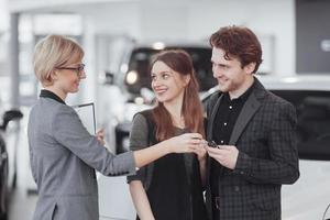 Buying their first car together. High angle view of young car salesman standing at the dealership telling about the features of the car to the customers photo
