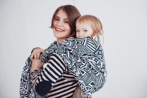 Modern young mother carrying her baby in a sling photo