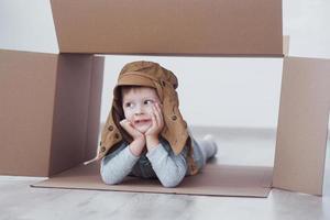 niño niño en edad preescolar jugando dentro de la caja de papel. infancia, reparaciones y nuevo concepto de casa. foto
