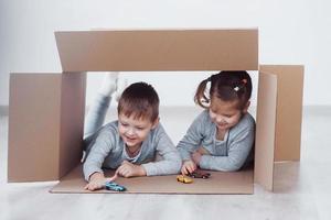dos niños pequeños niño y niña jugando autos pequeños en cajas de cartón. foto de concepto. los niños se divierten. foto de concepto. los niños se divierten