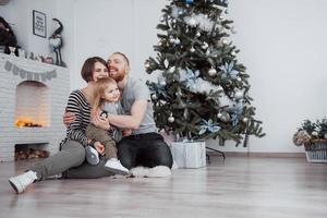 feliz navidad y próspero año nuevo hermosa mamá, papá e hija están usando una computadora portátil y sonriendo mientras están sentados cerca de los regalos de navidad foto