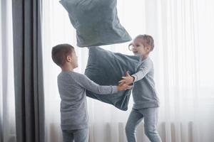 niño y niña organizaron una pelea de almohadas en la cama del dormitorio. los niños traviesos se golpean las almohadas. les gusta ese tipo de juego foto
