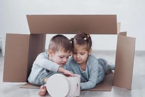 dos niños pequeños, niño y niña jugando en cajas de cartón. foto de concepto. los niños se divierten