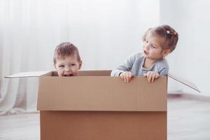 dos niños pequeños, niño y niña, se acaban de mudar a una nueva casa. foto del concepto .. los niños se divierten.