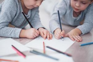 Children lie on the floor in pajamas and draw with pencils. Cute child painting by pencils.Hand of child girl and boy draw and paint with crayon. Close up view photo