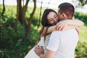 feliz y joven pareja embarazada abrazándose en la naturaleza. momentos romanticos foto