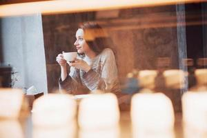 Beautiful young woman enjoying coffee cappuccino with foam near window in a cafe photo