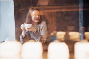 Hermosa joven disfrutando de café capuchino con espuma cerca de la ventana en un café foto